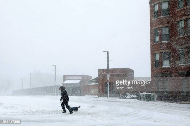A man crosses a street with his dog against heavy winds and blowing snow as Winter Storm Skylar bears down on March 13 2018 in Boston Massachusetts...