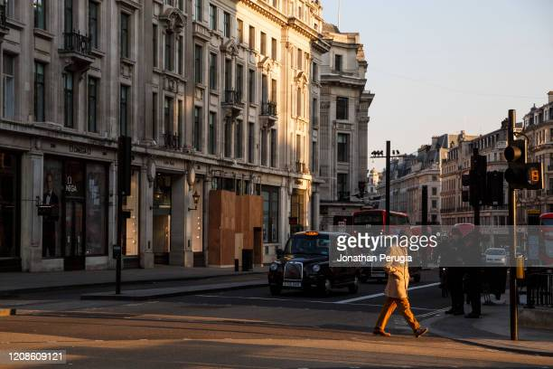 Man crosses an eerily quiet Regent Street in front of vacant taxis in the early evening at Oxford Circus in London on March 27th, 2020. The centre of...