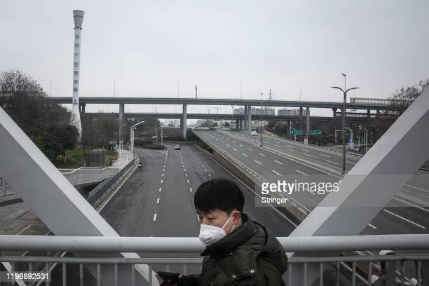 Man crosses an empty highway on January 27, 2020 in Wuhan, China. As the death toll from the coronavirus reaches 80 in China with over 2700 confirmed...