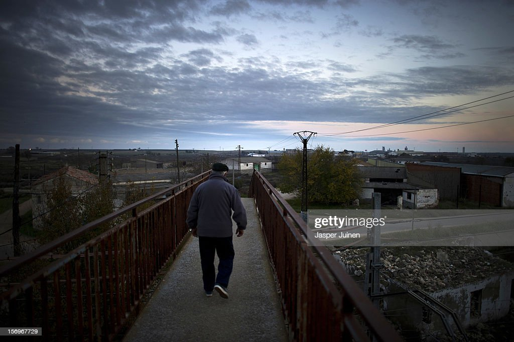 A man crosses an old bridge leading to the otherside of the railroad track on November 22, 2012 in Villacanas, Spain. During the boom years, where in its peak Spain built some 800,000 houses a year accompanied by the manufacturing of millions of wooden doors where needed, the people of Villacanas were part of Spain's middle class enjoying high wages and permanent jobs. During the construction boom years the majority of the doors used within these new developments were made in this small industrial town. Approximately seven million doors a year were once assembled here and the factory employed a workforce of almost 5700 people, but the town is now left almost desolate with the Villacanas industrial park now empty and redundant. With Spain in the grip of recession and the housing bubble burst, Villacanas is typical of many former buoyant industrial Spanish towns now struggling with huge unemployment problems.