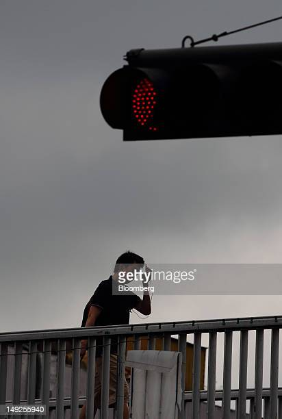 A man crosses an overpass under a traffic signal in Seoul South Korea on Tuesday July 24 2012 South Korea's economy grew at the slowest pace in...