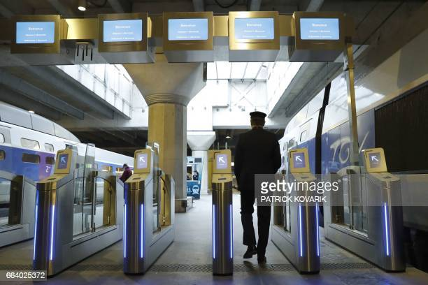 A man crosses antifraud gates at the Montparnasse railway station in Paris on April 3 2017 French national rail operator SNCF installed new ticket...