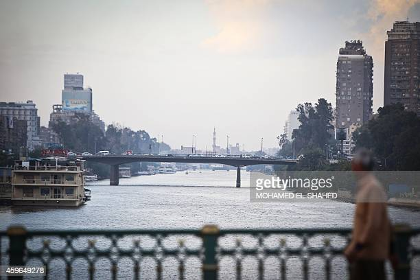 A man crosses Egypt's Nile river on the Galaa bridge in Cairo on November 27 2014 Falling tourist revenues and slowing investments have left Egypt's...