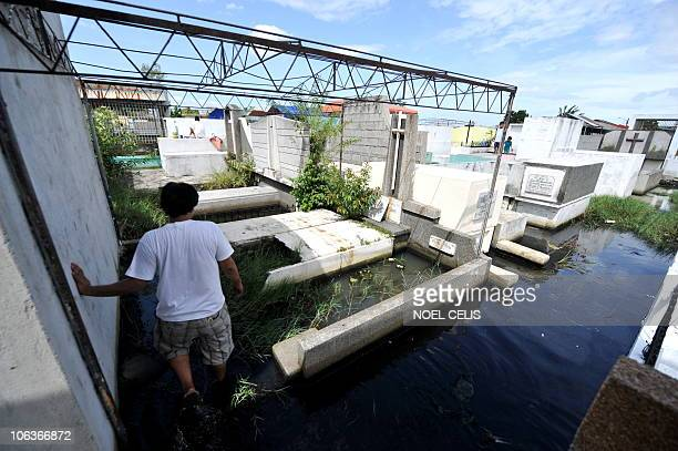 A man crosses flood water coming from an overflowing fishpond to clean and repaint the tomb of a departed relative in a cemeterty in Ubando Bulacan...