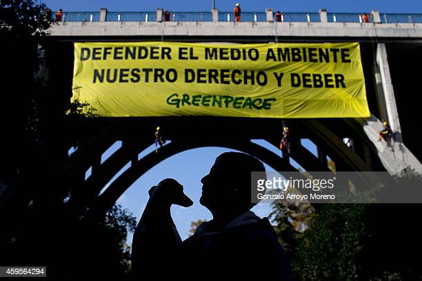 A man crosses Segovia street holding his dog as climbers of Greenpeace hang a banner from the Segovia Viaduct supporting the right and the duty to...