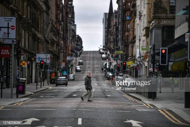 Man crosses the empty St Vincent Street during the Coronavirus crisis on April 1, 2020 in Glasgow, Scotland. The Coronavirus pandemic has spread to...