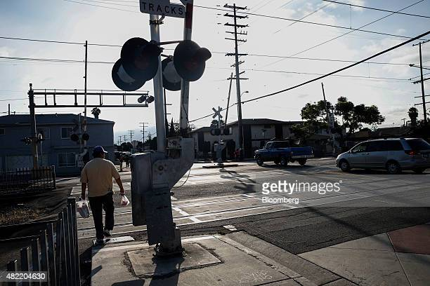 A man crosses the Metro Blue Line light rail tracks in Compton California US on Monday July 6 2015 It can be a letdown for LA Hood Life Hip Hop Tours...