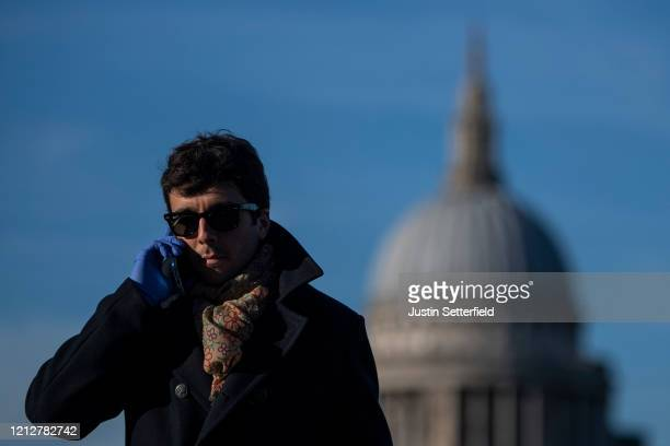 Man crosses the millennium bridge in front of St Pauls Cathedral wearing rubber gloves for protection against the corona virus on March 16, 2020 in...