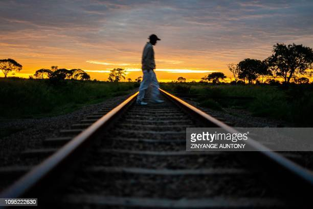 Man crosses the railway line and wait for a commuter train in the morning on January 29, 2019 in Cowdray Park township, in Bulawayo, Zimbabwe. -...