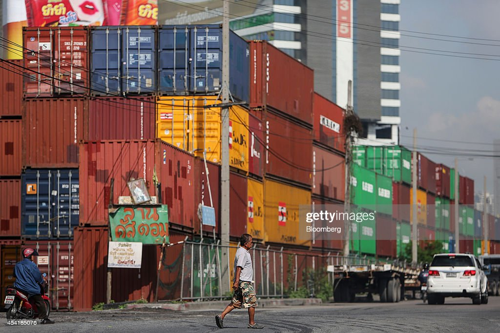 A man crosses the road as containers sit stacked at the Custom Global Service Co. container depot in Bangkok, Thailand, on Monday, Aug. 25, 2014. Thailand's trade figures are scheduled for release on Aug. 27. Photographer: Dario Pignatelli/Bloomberg via Getty Images
