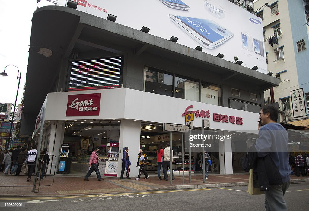 A man crosses the road in front of a Gome-branded store in the district of Tsuen Wan in Hong Kong, China, on Monday, Jan. 21, 2012. Gome Electrical Appliances Holding Ltd.'s stocks tumbled in Hong Kong after the company confirmed a report it is closing Gome-branded stores in the city. Photographer: Jerome Favre/Bloomberg via Getty Images