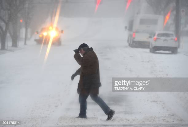 A man crosses the road in Greenwich Connecticut on January 4 2018 The US National Weather Service warned that a major winter storm would bring heavy...