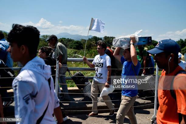 A man crosses the Simon Bolivar International bridge from Cucuta Colombia to San Antonio Tachira Venezuela with a white flag and a Tshirt reading I...