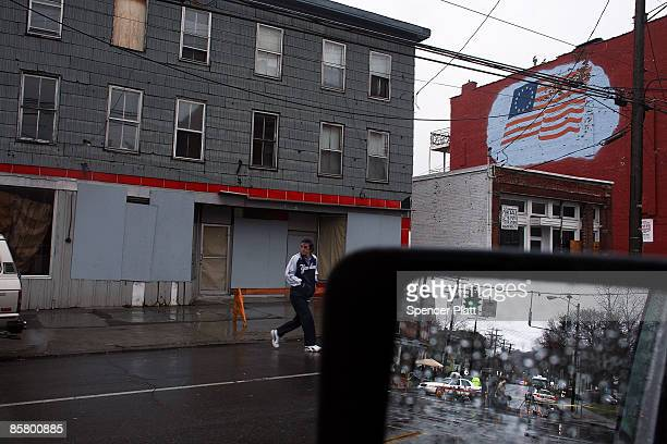 Man crosses the street beside the site where a gunman killed 13 people in an immigration community center yesterday April 4, 2009 in Binghamton, New...