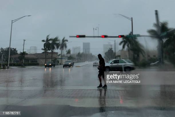 TOPSHOT A man crosses the street during a pouring rain in Fort Lauderdale Florida on September 2 2019 Monster storm Dorian stalled over the Bahamas...