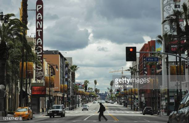 Man crosses the unusually quiet Hollywood Boulevard near the shuttered Pantages Theatre as the coronavirus pandemic continues on March 25, 2020 in...