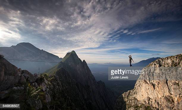 man crosses vast canyon on wire - risk stock pictures, royalty-free photos & images