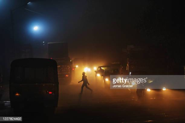 Man crossing a road in one of Kolkata's most polluted areas, the Garden Reach Dock area, where the AQI measures up to 850. According to the World...