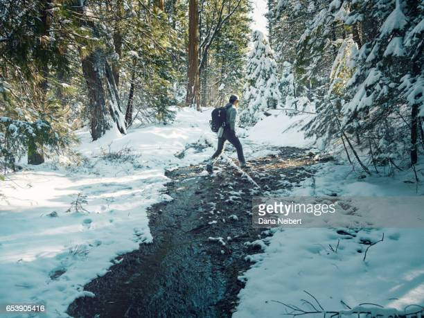 Man crossing a small stream in Yosemite National Park