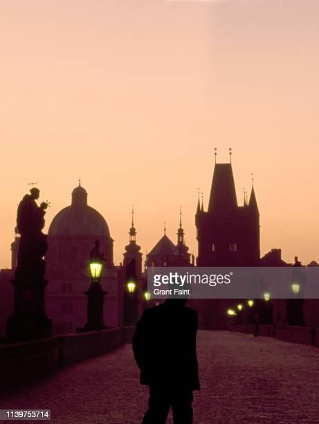 man crossing bridge at dusk. - charles bridge stock pictures, royalty-free photos & images