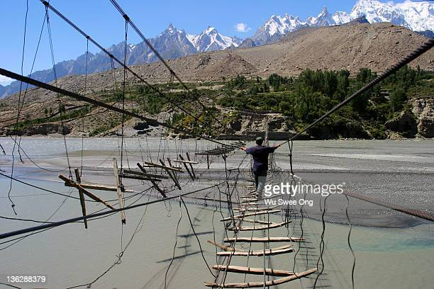 man crossing hussaini bridge - gilgit baltistan stock pictures, royalty-free photos & images