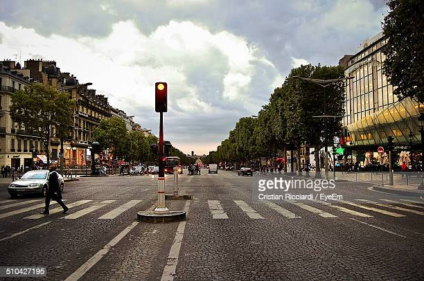 man crossing road along buildings and trees - road signal stock pictures, royalty-free photos & images
