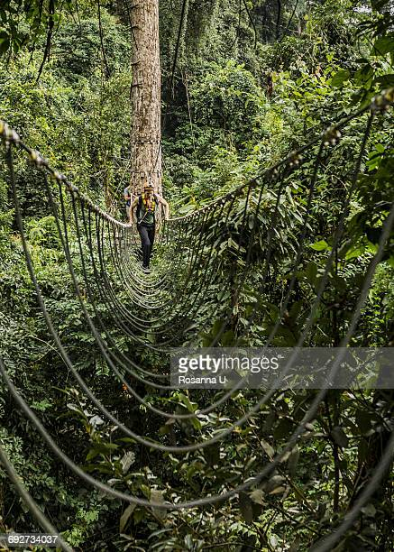 Man crossing rope bridge in forest, Ban Nongluang, Champassak province, Paksong, Laos