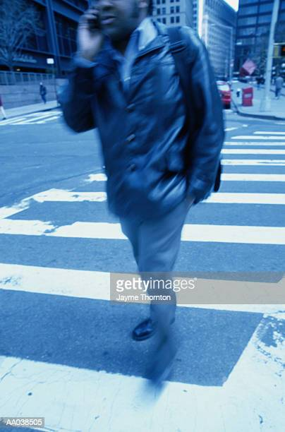 Man crossing street, using mobile phone, mid section (blurred motion)