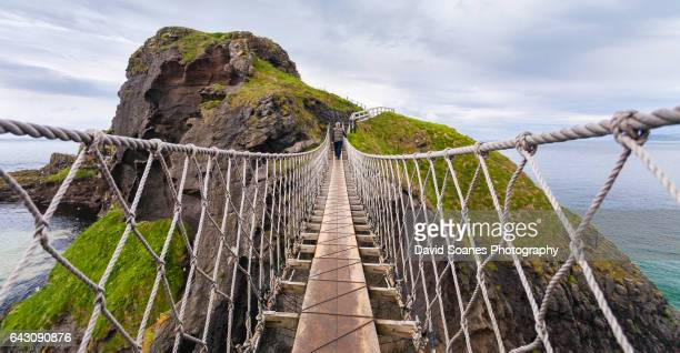 a man crossing the carrick-a-rede rope bridge in antrim, northern ireland - northern ireland stock photos and pictures