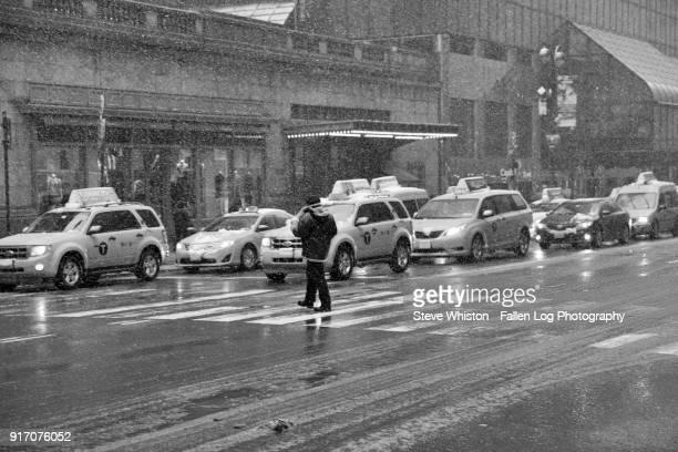 man crossing the street in front of taxis at grand central station in rain and snow in manhattan - grand central station manhattan - fotografias e filmes do acervo