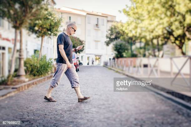 Man crossing the street while looking at his phone