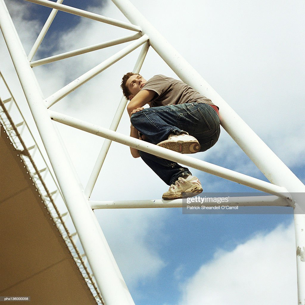 Man crouched on bars : Stockfoto