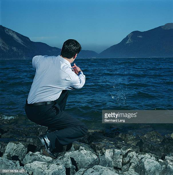 Man crouching at edge of lake to skim stone on water, rear view