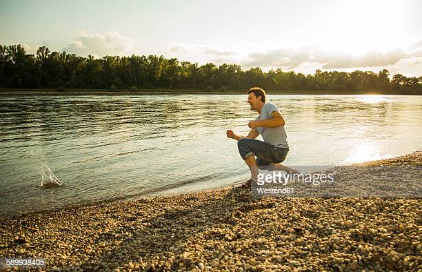 Man crouching at riverside throwing pebbles into the water