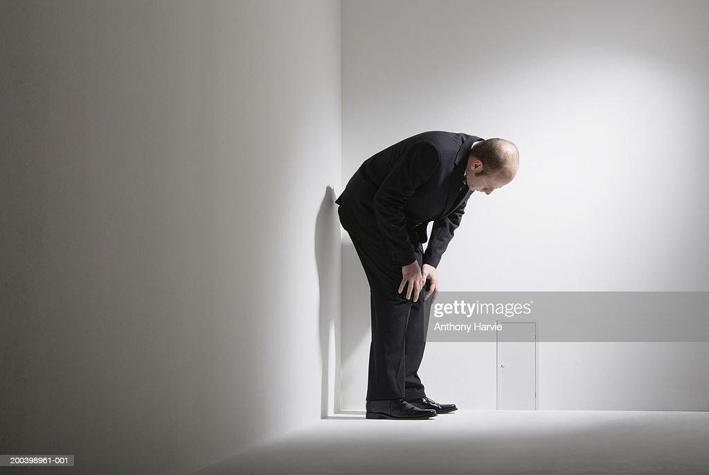 Man Crouching By Small Door In Room