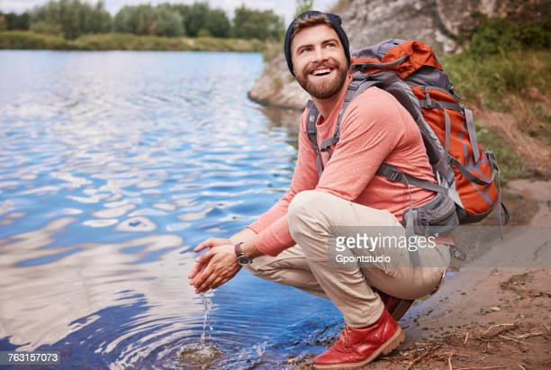 Man crouching by waters edge scooping up water in hands, Krakow, Malopolskie, Poland, Europe