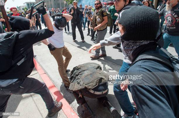 A man crouching for cover gets hit with a bike lock as multiple fights break out between Trump supporters and antiTrump protesters in Berkeley...