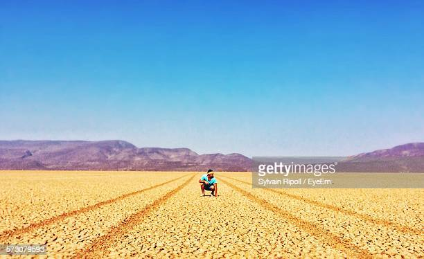 man crouching on desert against clear blue sky - djibouti stock pictures, royalty-free photos & images