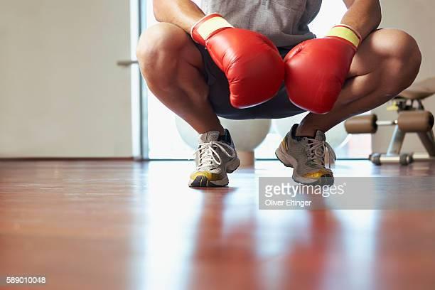 man crouching wearing boxing gloves - oliver eltinger stock-fotos und bilder