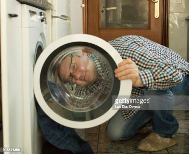 man crouching while loading clothes
