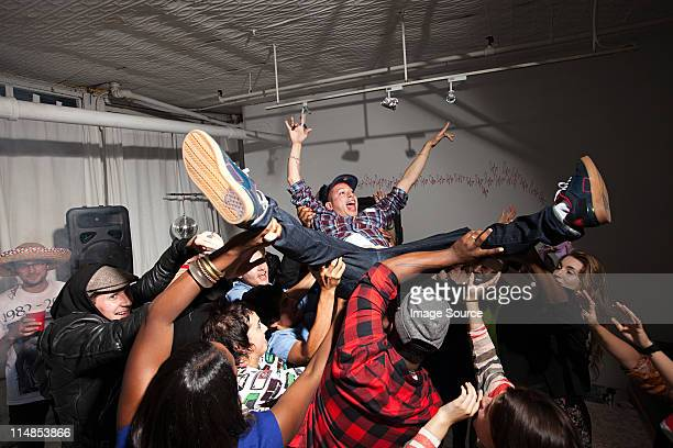 Man crowd surfing at party