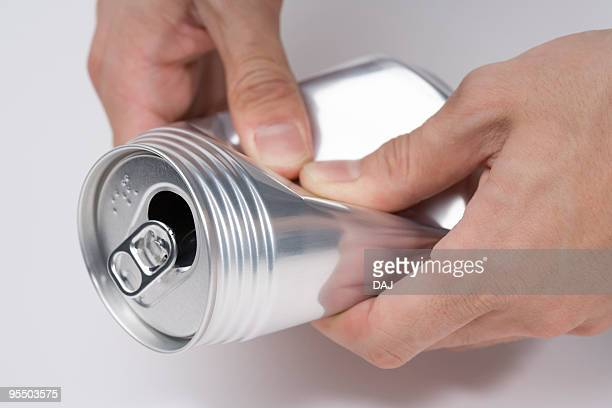 Man crushing a can, close up, white background