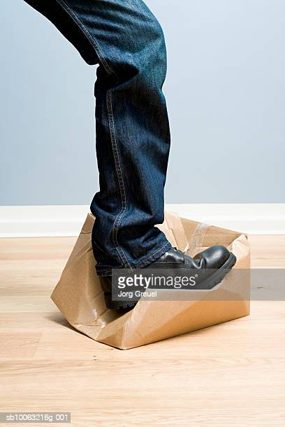 Man crushing cardboard box with foot, low section