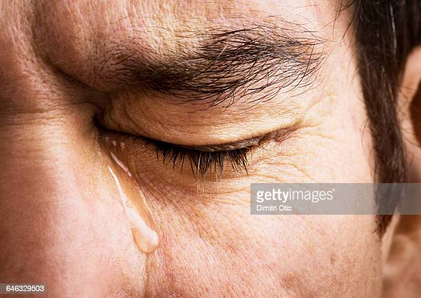 Man crying, close-up of eye and tear