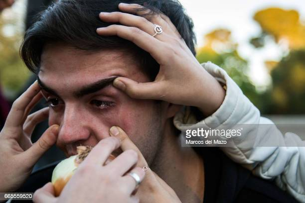 A man crying while his friends hold and onion near his eyes during an event organized through Facebook under the name 'Gathering for crying'...