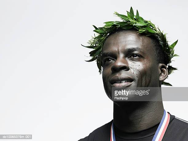 Man crying with crown of leaves on head, wearing medal, close-up