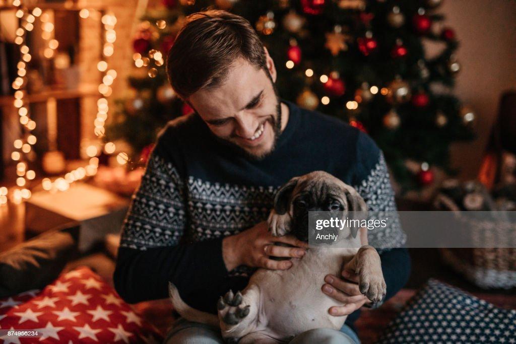 Man cuddling dog and enjoying Christmas holiday : Stock Photo