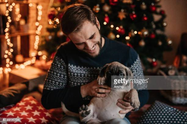 man cuddling dog and enjoying christmas holiday - happy new month stock photos and pictures