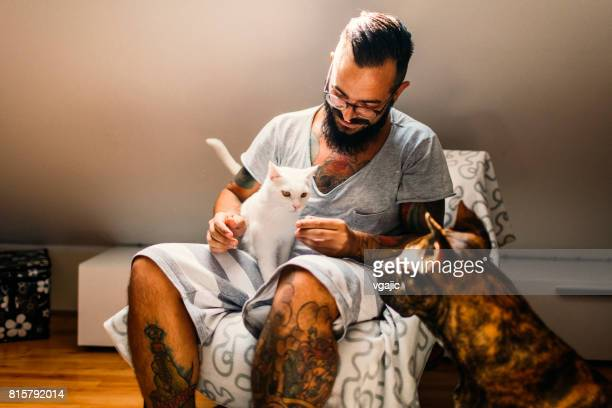 Mann mit seiner Katze und seinem Hund kuscheln