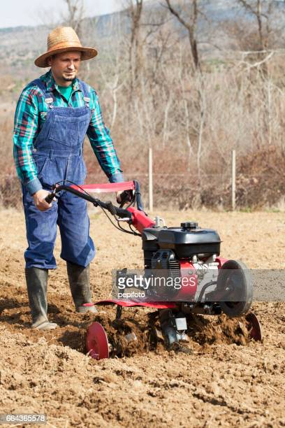 man cultivates the land with the cultivator - tiller stock photos and pictures